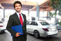 Salesman in a car showroom Royalty Free Stock Images
