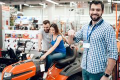 Salesman is posing with couple of clients and keys for cleaning machine in power tools store. Salesman in checkered shirt is posing with couple of clients and stock photos
