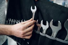 Salesman is showing bearded client set of wrenches in power tools store. royalty free stock images