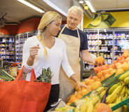 Salesman Choosing Fresh Oranges For Female Customer. Mature salesman choosing fresh oranges for female customer in grocery store stock images