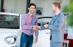 Salesman and client at the car saloon. Sitting, gesturing and presenting selling conditions Royalty Free Stock Photos
