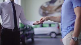 Salesman and client shake hands. Salesman gives keys from the car to client stock video