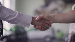 Salesman and client shake hands. Salesman gives keys from the car to client stock video footage