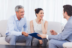 Salesman and clients talking and laughing together on sofa. In home royalty free stock image