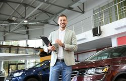 Salesman with clipboard in modern dealership. Salesman with clipboard in modern car dealership royalty free stock images