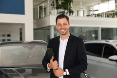 Salesman with clipboard in modern salon. Salesman with clipboard in modern car salon stock photo