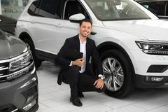 Salesman with clipboard near new car. In salon royalty free stock image