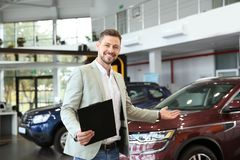 Salesman with clipboard. In modern car dealership royalty free stock photography