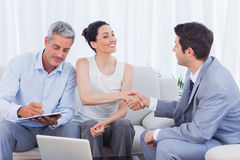 Salesman closing a deal with a couple. Sitting on couch Stock Photo
