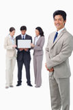 Salesman with colleagues and laptop behind him Royalty Free Stock Images