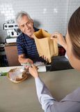 Salesman Collecting Cash While Passing Grocery Bag Royalty Free Stock Photography