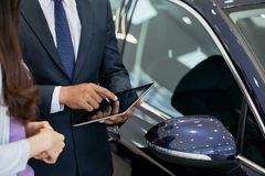 Salesman consulting client. Cropped image of car dealership salesman showing information about car on tablet to customer stock photography
