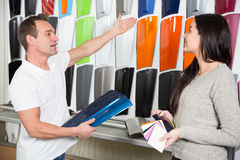Salesman consulting a customer about car wrapping foils. In different colors stock image