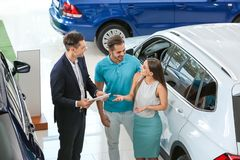 Salesman consulting young couple. In car salon royalty free stock photos