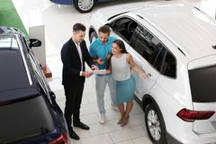 Salesman consulting young couple. In car salon stock image