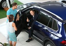 Salesman consulting young couple. In car salon royalty free stock image