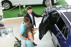 Salesman consulting young couple. In car salon royalty free stock photography