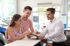 Salesman consulting young couple. In car salon royalty free stock photo