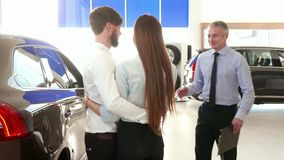 Salesman consults young couple at the car dealership. Mature salesman consulting young couple at the car dealership. Sales manager coming to his clients at the royalty free stock photos