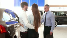 Salesman consults young couple at the car dealership stock video