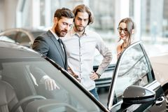 Salesman with couple in the car showroom. Car salesman showing car interior to a young couple clients in the showroom royalty free stock images