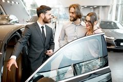Salesman with couple in the car showroom. Car salesman showing car interior to a young couple clients in the showroom stock photo
