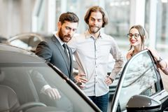Salesman with couple in the car showroom stock image