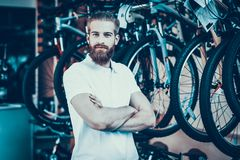 Salesman with Crossed Hands Poses in Bicycle Shop. Portrait of Cheerful Smiling Bearded Caucasian Man Wearing White T-Shirt Looking at Camera Standing Near royalty free stock photography