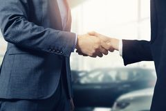 Salesman and customer handshake in car dea. Salesman and customer handshake after successful deal in car dealership royalty free stock images