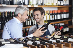 Salesman And Customer Holding Wine Bottles Stock Photos