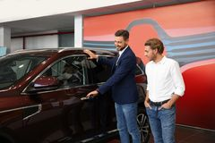 Salesman with customer in modern car. Dealership stock photo
