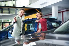 Salesman with customer in modern dealership. Salesman with customer in modern car dealership stock photography