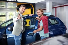 Salesman with customer. In modern car dealership royalty free stock image