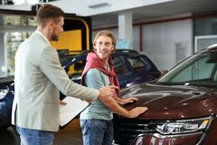 Salesman with customer. In modern car dealership royalty free stock images