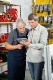 Salesman With Customer Using Digital Tablet. Senior salesman with customer using digital tablet in hardware store Royalty Free Stock Photography