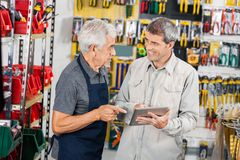 Salesman With Customer Using Digital Tablet In. Senior salesman with male customer using digital tablet in hardware store Royalty Free Stock Images