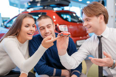 Salesman demonstrates toy car model to customers Stock Image