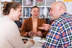 Salesman demonstrating to customer something. Positive salesman demonstrating to smiling customer something at table Stock Images