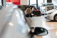 Salesman discussing with customer in car showroom. Salesman discussing with female customer while sitting in car showroom stock image