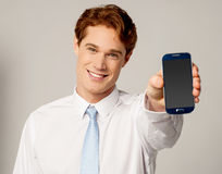 Salesman displaying newly launched mobile Stock Image