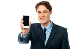 Salesman displaying newly launched mobile Stock Photography