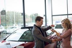 Salesman doing handshake while giving keys to customer Stock Photos