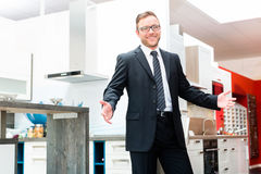 Salesman in domestic kitchen furniture showroom Stock Photos