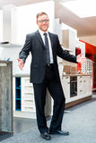 Salesman in domestic kitchen furniture showroom Royalty Free Stock Image