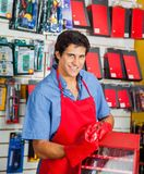Salesman With Drill Bit And Toolbox In Shop. Portrait of smiling young salesman with drill bit and toolbox in hardware shop Royalty Free Stock Images