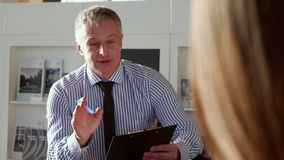 Salesman explaines contract conditions at the car dealership stock footage