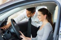 Salesman explaining car features customer stock photography