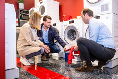 Salesman Explaining Product To Customers In Washing Machine Depa Royalty Free Stock Photos