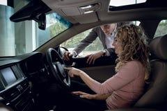 Salesman explaining to customer sitting in car royalty free stock photo