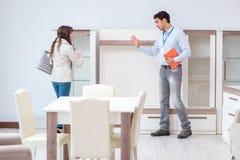 The salesman explaining to woman customer at furniture store. Salesman explaining to women customer at furniture store stock images